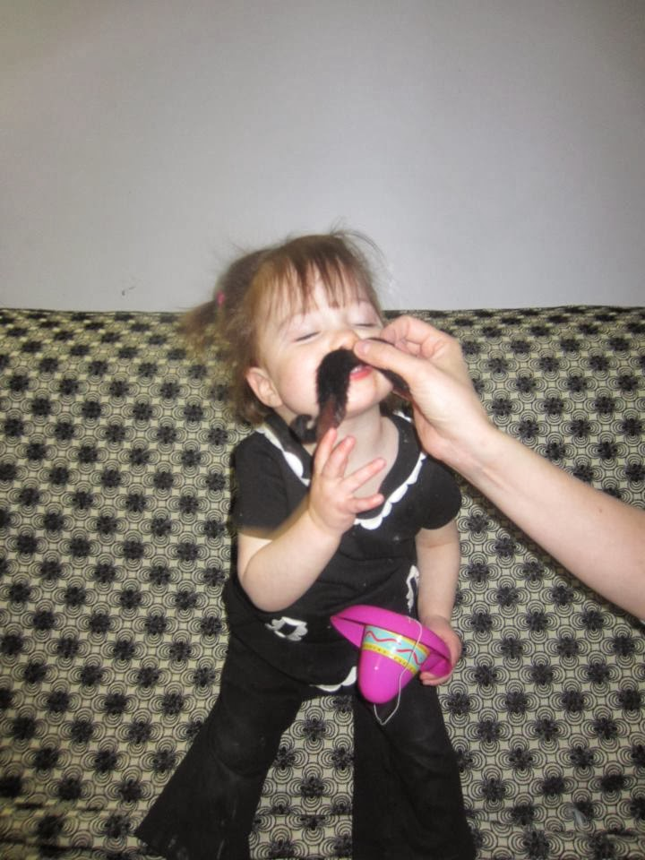 toddler girl with fake mustache and hat