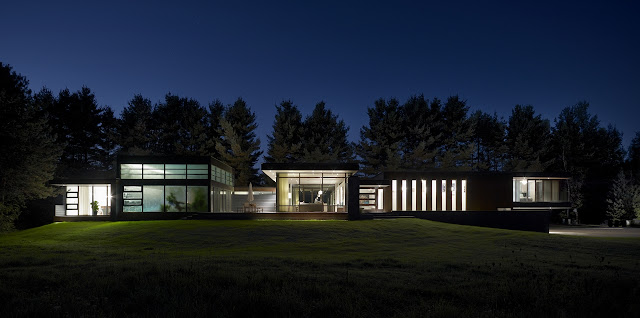 Picture of modern Clearview Residence on the small hill surrounded by the trees as seen at night