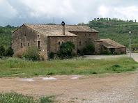 La façana nord de l'Alzina i al seu darrere, al fons, Cal Canonge i, entre els arbres, l'ermita de Sant Jaume de Riner