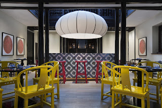 bright repainted yellow and pink ming style chairs inside modern space