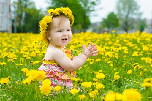Gambar bayi perempuan baermain di taman bunga