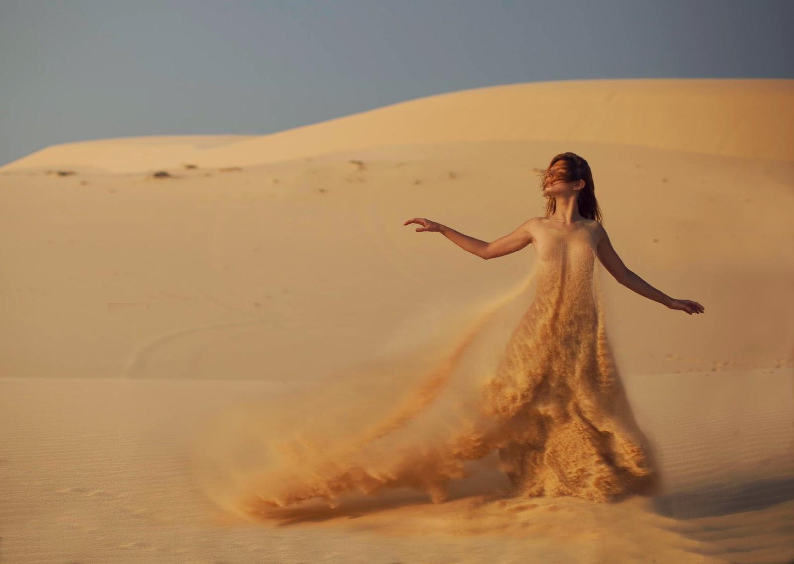 photo de Katerina Plotnikova d'une jeune femme nue recouverte de sable au milieu des dunes