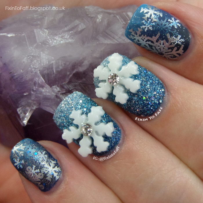 Snowflake nail art over blue gradient base with stamping and 3D nail charms.