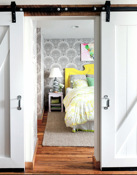 Barn doors open to reval a bedroom with gray Victorian inspired wallpaper, a white night stand, and a bed with yellow and white bedding and bright yellow molded headboard