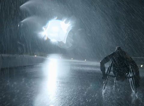 Screen grab from the C4 Paralympic Meet the Heroes promotion. A man in a sports wheelchair speeds around a track in the dark and pouring rain.