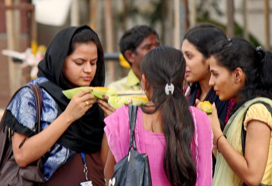 young girls eating bhutta corn on the roadside