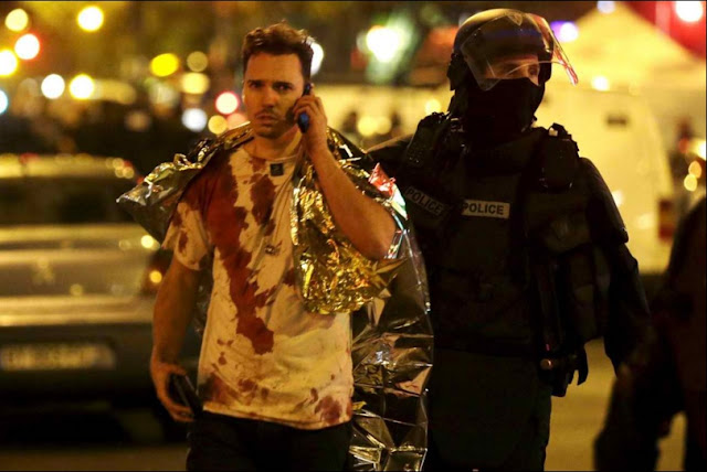 Paris Terrorist Attack - A Policeman assists a blood-covered victim