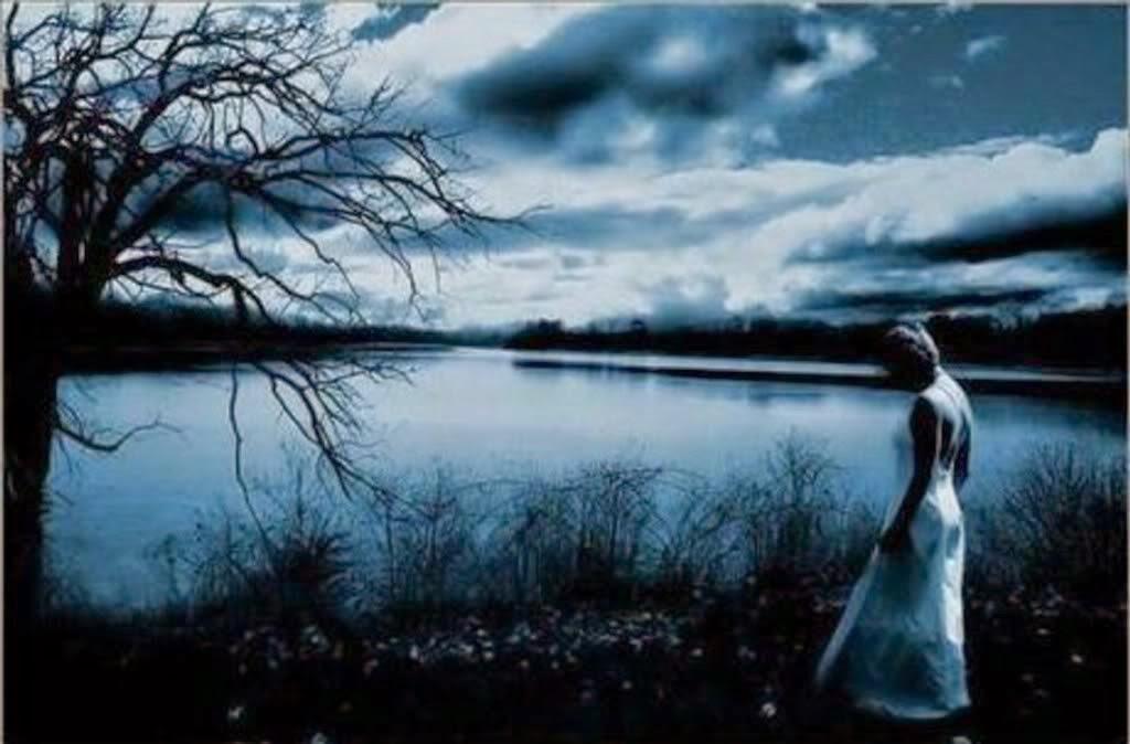 Imagen de una chica gótica con vestido blanco caminando a las orillas de un lago con un paisaje azulado de fondo.