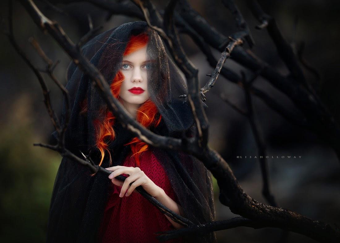 photo de Lisa Holloway représentant le portrait une jeune femme rousse en robe rouge derrière des branches
