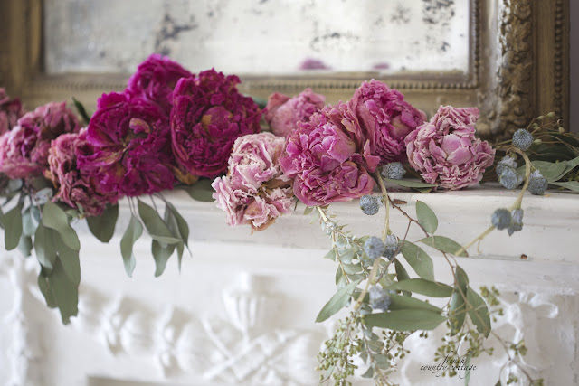 Dried peonies on a vintage mantel with gold mirror