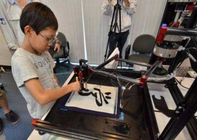 SEORANG budak lelaki mencuba robot kaligrafi di sebuah bengkel sains untuk murid sekolah rendah di Universiti Keio, Yokohama, dekat Tokyo, Jepun kelmarin.