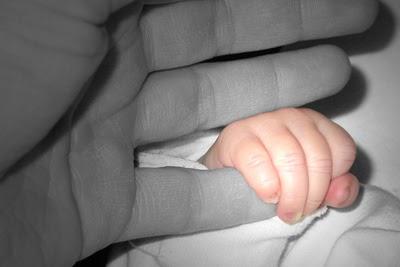 Hand eines Baby umschließt einen kleinen Finger