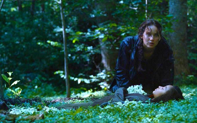 Na imagem: Em um cenário de floresta Katniss (uma garota de jaqueta escura e trança) está ajoelhada olhando pra algo a frente, o rosto dela só expressa atenção e talvez cansaço. Em frente a ela uma garotinha está deitada na grama morta com uma expressão de paz e as mãos sobre o peito onde está um buquê de flores branca.