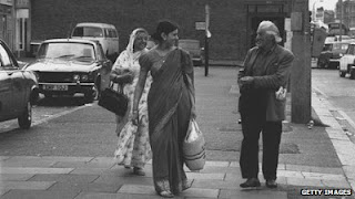 Indian women wearing saris walking down the road alongside a white man