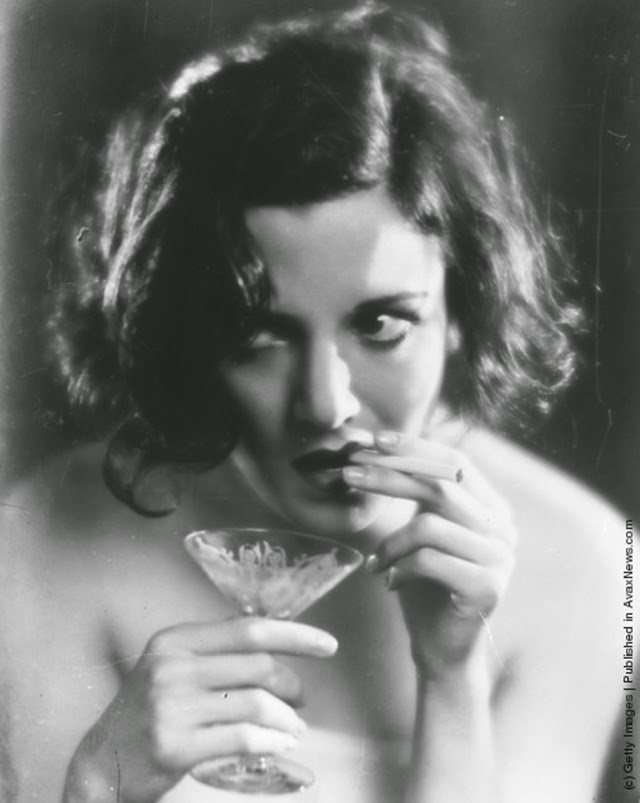 Woman smokes a cigarette while holding a cocktail glass in the other