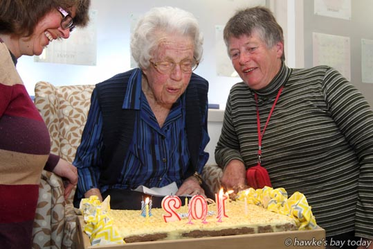 Naomi Merrall, 102, blowing out candles on her birthday cake at Gracelands Lifestyle Care and Village, Hastings, with granddaughter Angela Allen, Hastings, and daughter Linda Williamson, Taradale, Napier. photograph