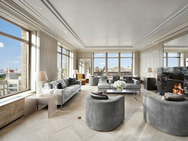 Living room in a NYC penthouse with light wood herringbone floor, grey sofas and armchairs and a marble fireplace mantel