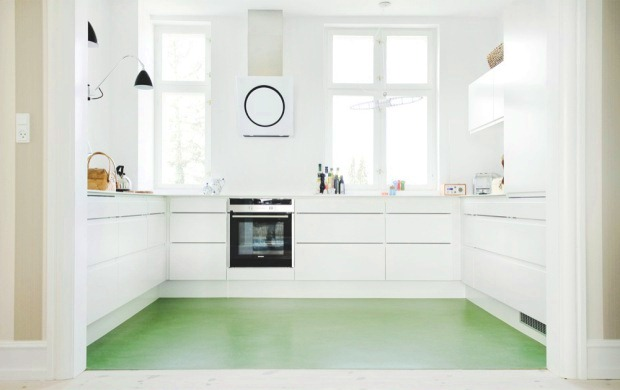 small white kitchen with green linoleum floor and black appliances