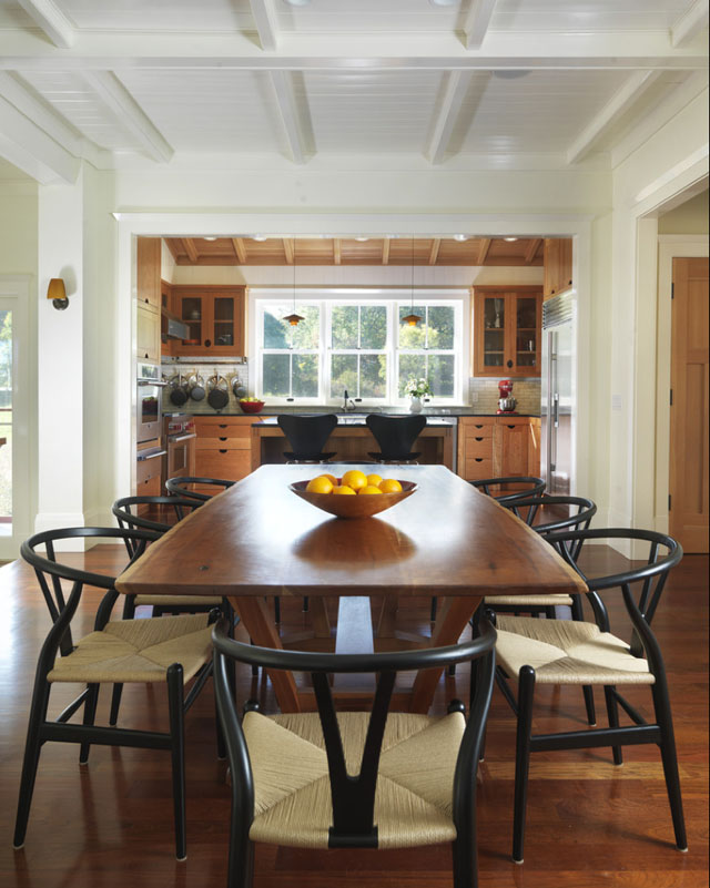 Black Oak Wishbone Chairs with Natural Papercord Seats are used in this transitional kitchen and dining room (Architecture by Union Studio, Architecture and Community Design).