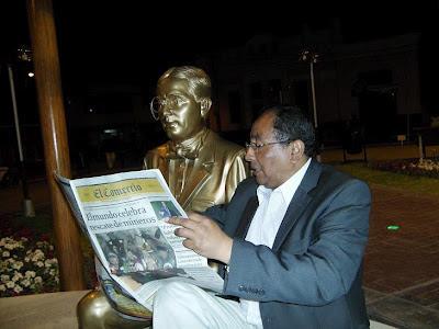 El periodista lee el diario El Comercio ante el busto del escritor peruano Abraham Valdelomar en Ica.
