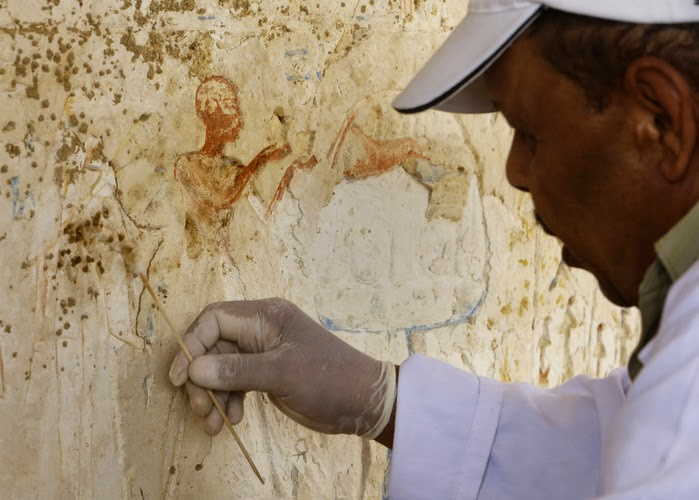 An Egyptian conservator carefully works at a newly-discovered tomb dating back to around 1,100 BC at the Saqqara archaeological site near to a previously-discovered tomb of the head of the army