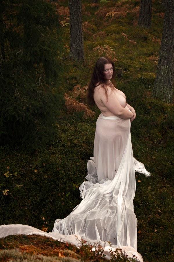 femme nue drapée à partir des reins dans un long voile blanc posant dans la nature