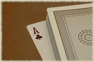 Foto: Ein Stapel Spielkarten mit der Rückseite nach oben. Die unterste Karte ist umgedreht und schaut heraus, so dass sie als Kreuz-As zu erkennen ist.