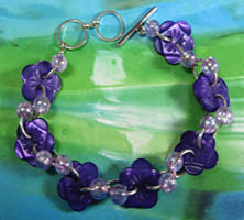 Pretty bracelet has bright purple flower buttons with small light purple accent beads in twist design