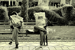 Untitled photograph of two people reading newspapers on a park bench by Hamed Saber on Flickr
