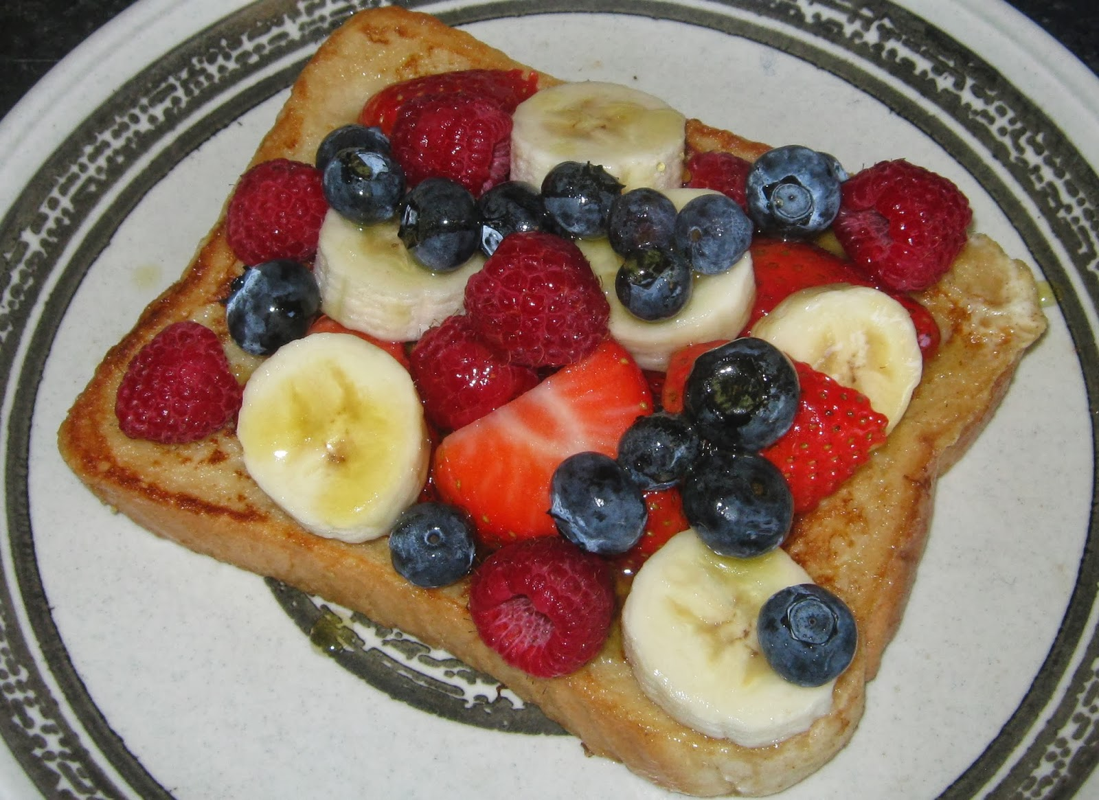 French toast with bananas, blueberries, strawberries and raspberries