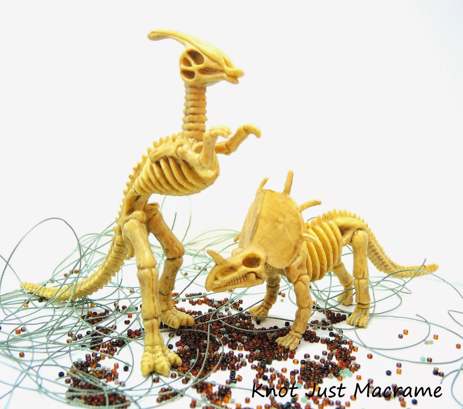 Dinosaur skeleton models messing about in beads and cord.