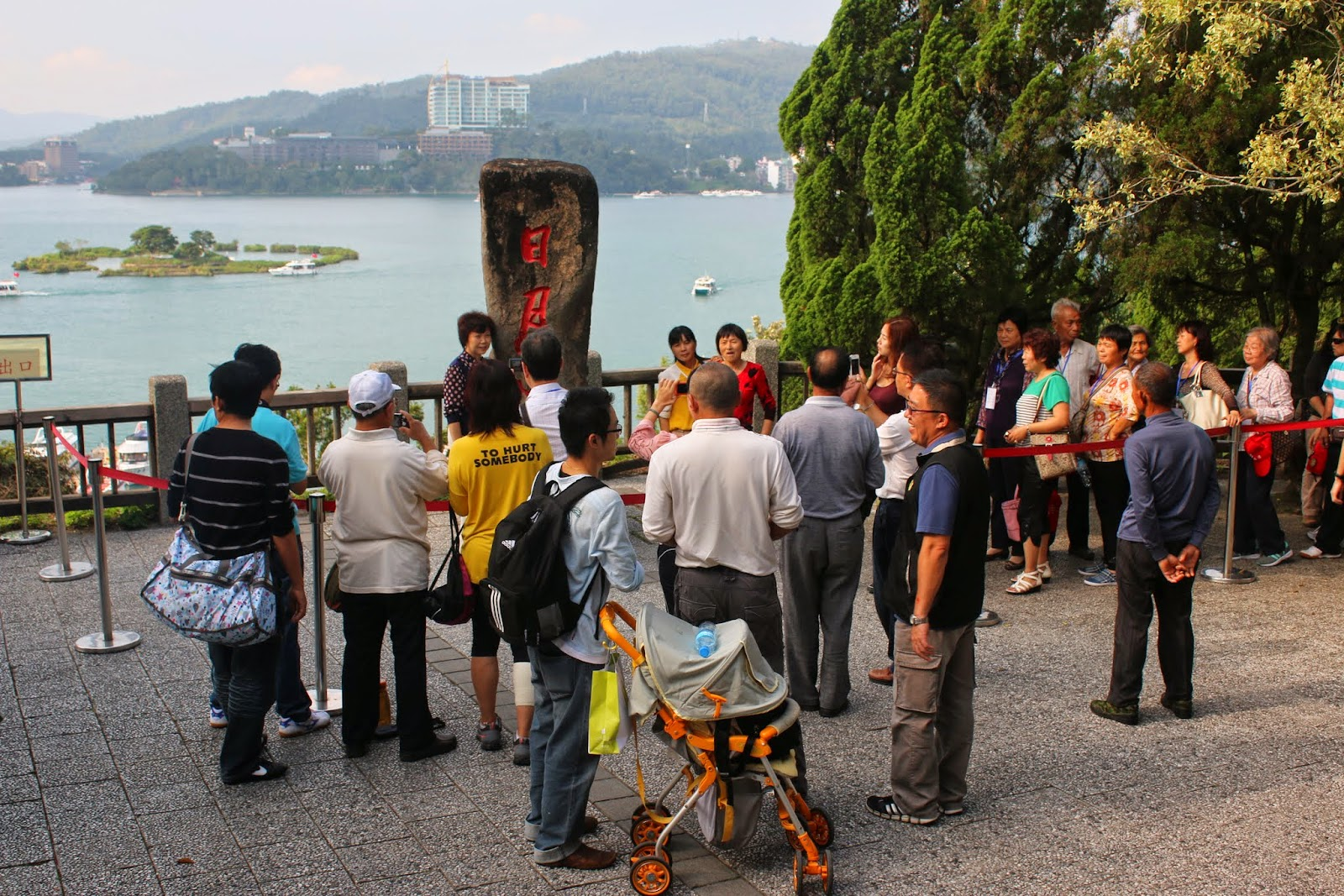 Visitors queue for their photo taking with the stone sign of Sun Moon Lake at Syuanguang Temple in Taiwan