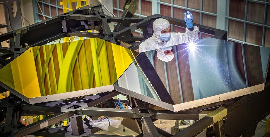 "Inside NASA's Goddard Space Flight Center's giant clean room in Greenbelt, Md., JWST Optical Engineer Larkin Carey examines two test mirror segments recently placed on a black composite structure. This black composite structure is called the James Webb Space Telescope's ""Pathfinder"" and acts as a spine supporting the telescope's primary mirror segments. The Pathfinder is a non-flight prototype. Credit: NASA/Chris Gunn"