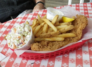 Fish basket with fries and a side of coleslaw.