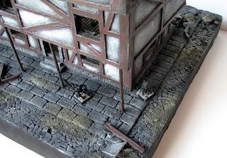 Makieta ulicy miasta Mordheim z figurkami krasnoluda oraz Skavena