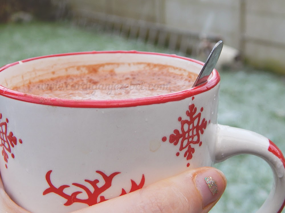Hot chocolate in a mug snow in the background