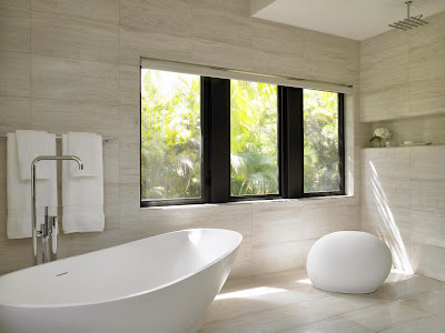 a muted and white bathroom design with contemporary bathtub and stone-like decoration by the window