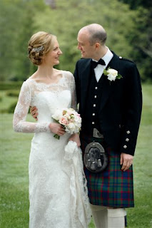 bride with vintage style hair holding her bouquet smiling at the groom wearing a kilt