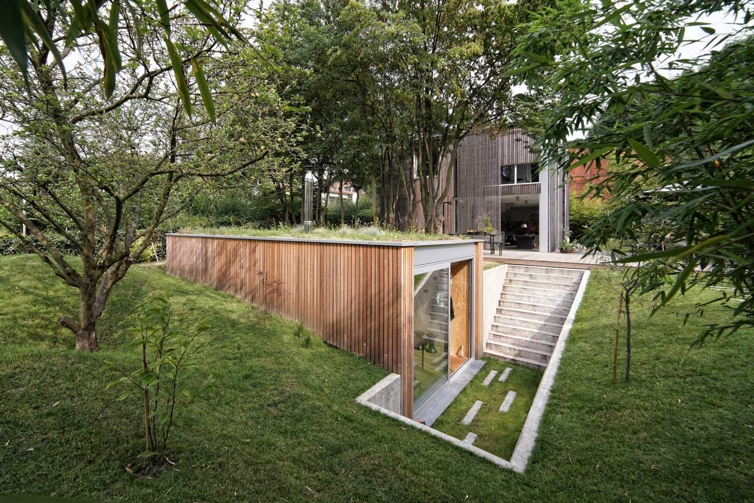 unique home design submerged under green roof atelier