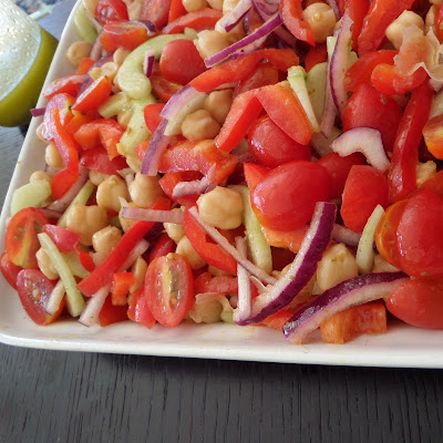 Greek Salad:  A fresh and delicious salad with tomatoes, cucumber, red onion, red bell pepper, and garbanzo beans tossed in a lemon and oregano dressing.