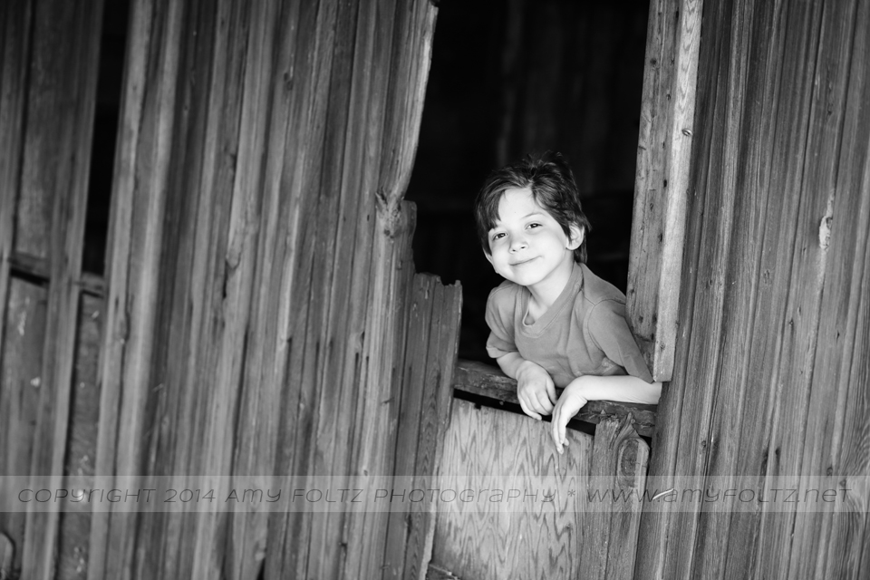 photo of a young boy inside an old barn