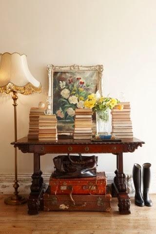 Oryginalna aranżacja dekoracji na rzeźbionym biurku, stare walizki, mosiężna lampa z abażurem, kalosze