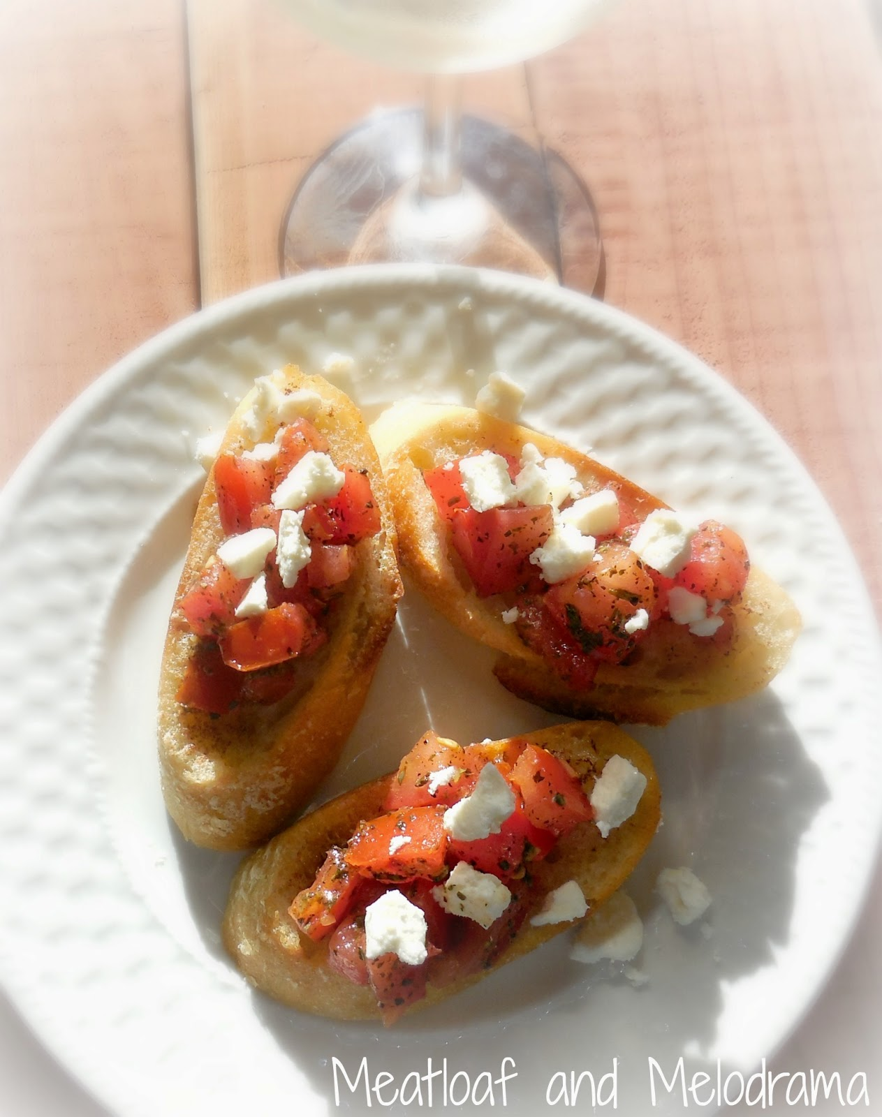 tomato bruschetta and feta cheese on a plate with wine