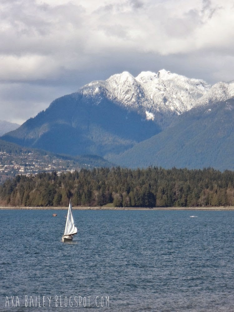 Sailboat in English Bay in front of mountains