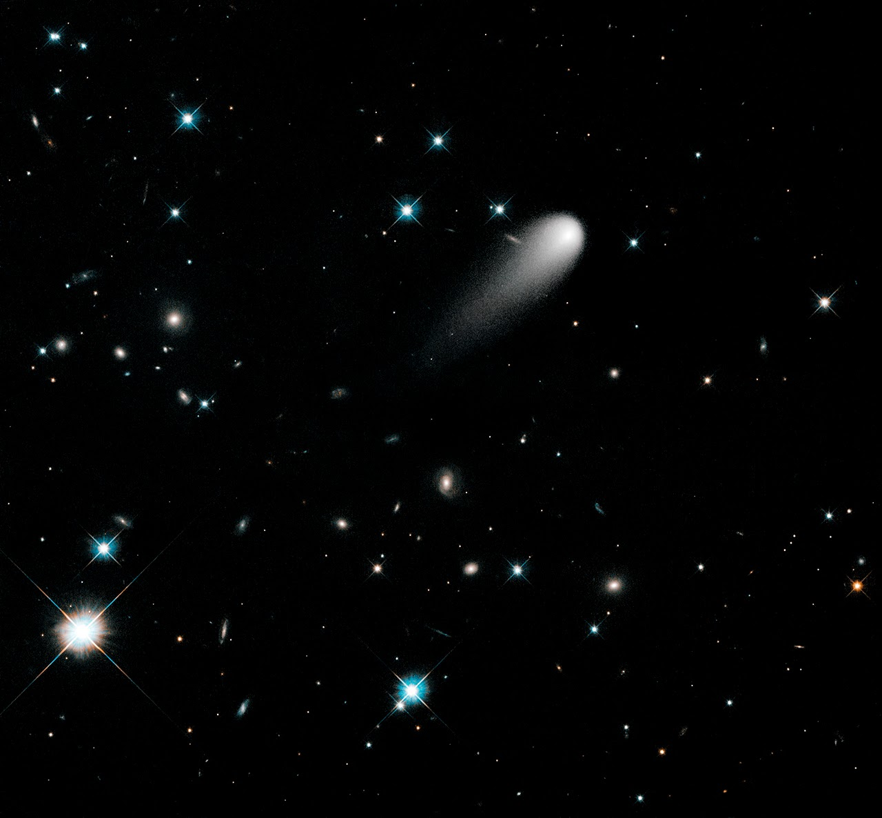 In this Hubble Space Telescope composite image taken in April 2013, the sun-approaching Comet ISON floats against a seemingly infinite backdrop of numerous galaxies and a handful of foreground stars. The icy visitor, with its long gossamer tail, appears to be swimming like a tadpole through a deep pond of celestial wonders.  In this composite image, background stars and galaxies were separately photographed in red and yellow-green light. Because the comet moved between exposures relative to the background objects, its appearance was blurred. The blurred comet photo was replaced with a single, black-and-white exposure.  The images were taken with the Wide Field Camera 3 on April 30, 2013. Credit: NASA, ESA, and the Hubble Heritage Team (STScI/AURA)
