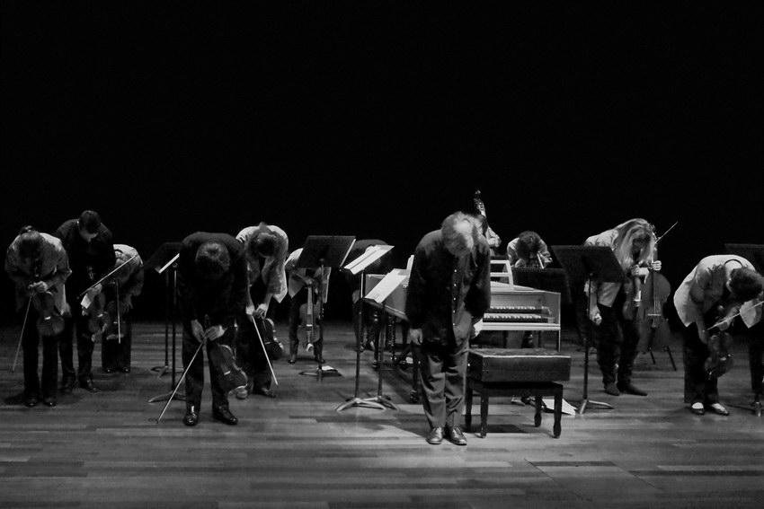 Elementos da orquestra de pé, de cabeça baixa, agradecendo ao público