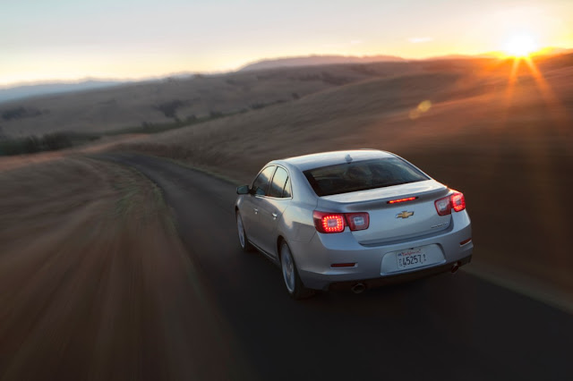 Rear 3/4 view of a silver 2013 Chevrolet Malibu Turbo driving on a rural road at sunset