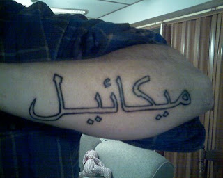 Guy with some Arabic Text Tattoo design on his forearms