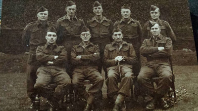 Nine men in military uniform, five standing, four seated in front, all on the elderly side except my grandad.