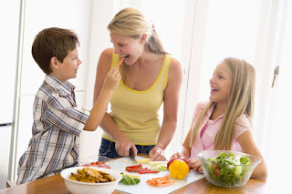 Mother preparing healthy foods with son and daughter